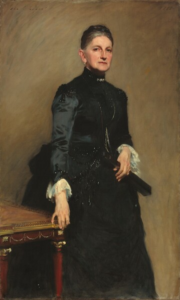 """Seen from the shins up, a woman with pale skin, iron-gray hair bound in a low, wide knot atop her head, and wearing a high-collared, long-sleeved black dress, stands next to a table against a caramel-brown wall in this vertical portrait painting. Her body is angled to our right and she looks out at us from the corners of her eyes with dark eyes under arched brows. She has a straight nose and slight jowls along her jaw line. Her thin, coral-red lips are set in a straight line. A round pearl hangs from the earlobe we can see and glints in her hair suggest pearls or other ornaments. Three jewels, also perhaps pearls, glisten at her high collar and black beads catch the light at the shoulders and cuffs of the puffy, long sleeves. The bottom edge of the tight-fitting bodice also seems to be beaded, and the full skirt flares out at the hips. The sleeves end with white, ruffled cuffs. She holds a closed black fan with her left hand, on our right, and wears a gold ring on that pinky finger. She stands just behind the corner of a cherry-red table edged with gold, to our left, and grips the corner with the fingertips of her opposite hand. The portrait is painted with loose but blended brushstrokes, giving it a soft look. The artist signed the painting in the upper left corner, """"John S. Sargent"""" with the date in the upper right, """"1888."""""""