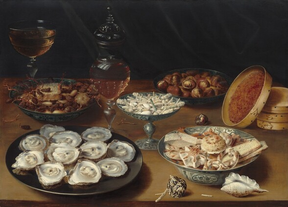 We seem to look slightly down onto five plates, bowls, and dishes are filled with oysters, raisins and prunes, figs, and sweets along with a wine glass, a glass decanter, a stack of round, wooden boxes, and two seashells arrayed on a wooden tabletop against a dark background in this horizontal still life painting. The scene is painted in warm tans, chestnut and cherry browns, creamy and bright whites with touches of muted blue in the decorations of two of the dishes. Closest to us to our left, eleven glistening oysters on the halfshell are arranged on a round, iron-gray dish. Also close to us, to our right, a white porcelain bowl with a wide, flaring lip is painted with blue flowers, and it is piled with light tan breads, rolls, and pastries. Two shells sit near that bowl: one shimmering, spiraling, ivory-colored shell with chocolate brown marks sits to our left and an elongated, white shell with a ruffle along its length sits in the lower right corner of the panel. Between and behind these two dishes is a vessel with a pedestal foot and a wide, shallow bowl, filled with white almonds and rods that have been covered with white sugar. In the back left, a dark gray bowl holds raisins and other dried fruit along with an object that could be a slice of bread or cheese. Opposite it, a similar dish holds brown figs that more closely resemble chestnuts. To the back right, the lid of one of the three round, shallow boxes stacked along the right edge of the composition leans against the pile. The inner lid is covered with quince paste, which resembles apricot preserves. One glass goblet with a wide bowl is nearly filled with amber-colored liquid in the back left corner, beyond the dried fruit. A glass decanter, also filled with gold-colored wine, sits to our left of the pedestal-footed vessel holding the sugared sweets, at the center of the composition. The still life is brightly lit from our left.