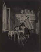A woman with light skin wearing a long, corseted dress with a full skirt and a wide-brimmed hat with feathers sits writing or drawing at a round table next to an open window in this vertical, black and white photograph. Light coming in through the window to our left creates slanting stripes of light and shadow across the table and the wall opposite us, suggesting it filters through blinds or slats. The woman sits in a straight-backed, wooden chair with a caned back, angled away to our right almost in profile. She looks down and bends slightly over the paper and pen. Her hair is pulled back in a bun at the back of her head under the hat, and her dark dress has a wide lace collar. The table is covered with a patterned cloth and holds a tall candlestick with a twisted candle, an ink bottle, a small, lidded jar, and a picture of a woman in a frame decorated with daisies. On the wall opposite us six photographs or drawings hang on the wall. Two show landscapes, three show a woman or women, and one shows a man. Three heart-shaped decorations tied with bows hang among the other papers and a bird cage hangs to our right. The wallpaper has a dense, formal, stylized floral pattern. The windowpanes swing into the room to our left, and a sliver of an open doorway lines the right edge. The top and bottom zones of the photograph are swallowed in deep shadow.