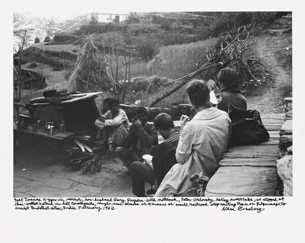 Poet Joanne Kyger in mirror, her husband Gary Snyder with notebook, Peter Orlovsky eating sweetcake, we stopped at Chai-wallah's stand in hill countryside, maybe near Almora or Kausani or small railroad stop waiting train on Pilgrimage to ancient Buddhist sites, India February 1962.
