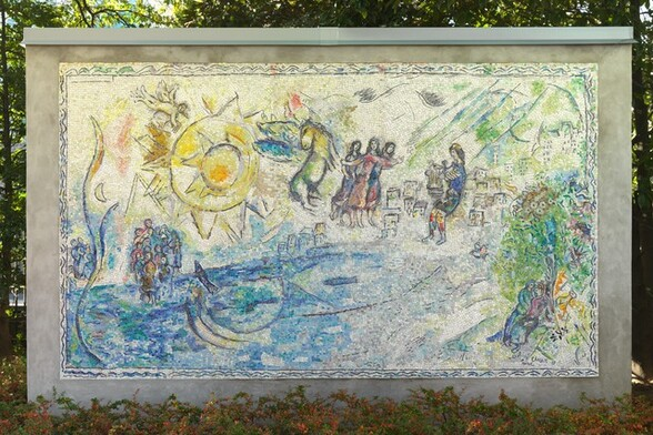 """Created with tiny, colored stones and glass, this mosaic shows groups of people along and near the edge of a brilliant, topaz-blue body of water with a large, lemon-colored, stylized sun in the sky in this horizontal composition. The aquamarine-blue and vibrant yellow along with lime-green, lilac-purple, oyster white, and teal used in the people and landscape give this work a shimmering look. A pair of people recline together under a tree in the lower right corner. A sheep stands nearby and a bird perches in the tree above. Beyond the tree and to our left, a cluster of box-like forms suggests a city in the distance. Larger in scale, so seeming closer to us, a man wearing a lapis-blue toga and a yellow cap holds a stringed instrument, a lyre, in front of his body. To the left, at the center of the composition, a trio of women each wearing amethyst-purple, magenta pink, or lapis-blue dresses stand close to each other. They have long, dark hair and their bodies and garments are outlined in black. Between them and the large sun to our left, a winged horse with a buttercup-yellow body and turquoise wings rears up. Near the upper left corner, the stylized sun is represented by a disc surrounded by pointed peaks, surrounded by a larger disc outlined with another ring of triangular points. A winged person holding a set of pan pipes flies above the sun to our left, over a small crescent moon below. Near the lower left corner, two groups of people gather around a body of bright blue water occupied by two fish. The artist signed and dated the work in the lower right corner: """"MArC ChAgAll 69."""" The mosaic is displayed outside in front of a screen of trees, with a band of bushes with green and orange leaves below."""