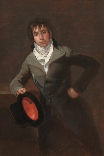 Shown from the knees up, a cleanshaven, young man with smooth, creamy skin wears an elephant-gray coat with wide lapels over a high collared, snowy white shirt, as he leans on his right elbow, to our left, against a surface and holds a tall, black, top hat so we see the crimson red interior in this vertical portrait painting. His body faces us and he looks slightly off to our left, as if just over our left shoulder, with dark eyes. He has a wide nose, his flesh-pink lips are closed, and he seems to have a faint five o'clock shadow on his square jaw and cleft chin. Sideburns come down past his ears and straight brown hair falls in long bangs over his forehead and around his eyes, though the rest of his hair seems to be cut short. The white shirt at his neck is striped faintly with light blue and red, and tied at a knot at his throat. The gray jacket has a black collar at the back and wide lapels that reach his shoulders. The jacket is fitted to his waist, where it is buttoned, and then seems to flare out into the shadows at his knees. Silver buttons gleam in the light from our left, down that side of the jacket. He left fist, on our right, rests against his hip as he leans on the opposite elbow, presumably on a ledge or high table. The background behind him is subtly streaked with brick and coffee brown. The red interior of the black top hat draws the eye in a palette dominated by brown, gray, and black.