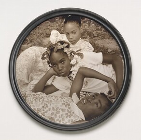 Three young Black girls lie on the grass in this closely cropped, sepia-toned, circular photograph so their faces roughly line up near the center. At the bottom of the composition, a girl, about ten years old, lies on her back and looks up into the sky. Her head, torso, and right arm are visible. She wears a floral-patterned dress and holds her right hand up to the top of her head. The second girl, also about ten years old, reclines on her right side behind the first girl, so she's angled to our left. She props her head in her right hand and looks steadily at us. Her face hovers at the center of the composition. She wears a white t-shirt and a garland encircles her head. The third girl, at the top of the composition, seems to prop her body up on her left elbow. She wears a floral dress and looks down and to our right. Grass and paving rocks fill the space behind her.