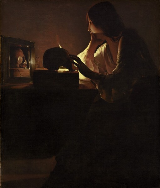 A young woman with pale skin sits at a table in a darkened room. Long chestnut hair drapes over her shoulder and her deep, cream-colored, long-sleeved garment is open at her neck. She rests her chin in her right hand, farther from us, as her left reaches for a skull placed on a thick book on the table in front of her. The scene is illuminated by a single candle mostly out of sight behind the skull. Shown in profile, she looks into a small mirror next to the skull, which reflects that object and the book.
