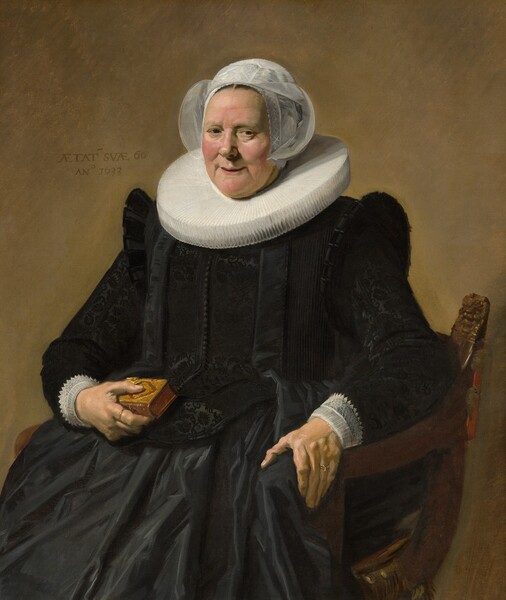 """This vertical portrait shows an older woman wearing a full, long-sleeved, rich black dress with a wide white ruff at her neck and white lace cuffs at her wrists. She sits in a curving, low-backed wood chair against a pale brown background. Her body and the chair are angled slightly to our left and she looks directly at us. Her skin is fair, and she has small eyes, pink, rounded cheeks, and a wide chin. Her lips are parted in a slight smile and her hair is covered by a starched, sheer white cap that flares at the sides. The ruff around her neck is gathered in accordion-like, narrow figure-eight folds, and it extends flat and stiff, nearly to her shoulders. Close inspection reveals that the dress is woven with a black-on-black brocade pattern and has a line of small black buttons down the front. She holds a small brown leather book tooled with gold ornament in her right hand, on our left, and her opposite hand rests on the arm of the chair. She wears a gold ring on each hand. An inscription is painted to our left of her head: """"AETAT SVAE 60 ANo 1633."""""""