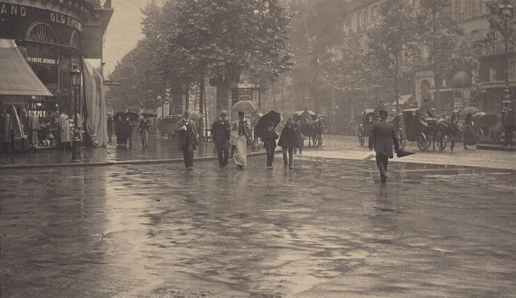 In this black and white horizontal photograph, an urban street corner is busy with life on a rainy day. The photograph is roughly divided in half horizontally so the lower half shows a the wet pavement of a wide intersection, momentarily clear of people, where two streets meet. The upper half shows shops and buildings along a tree-lined street that runs from the right and recedes at a low angle into left side of the picture, while the intersecting street, which occupies foreground and the bottom half of the image, comes from the left to form a T with the other street. Along the street, there are about 10 people are on foot, while several horse-drawn carriages with large, spoked wheels, driven by caped and top-hatted men, pass through or are parked alongside the curb. Most of the pedestrians hold up dark umbrellas and start to cross the intersection across from us, while only one man, without an umbrella, crosses the street walking away with his back toward us. All of the men wear dark suits with jackets, vests, white shirts with bowtie, and formal hats. A woman accompanied by an umbrella-less man wears a long skirt and matching thigh-length coat over a contrasting buttoned bodice. She holds up her skirts in one hand and her umbrella in the other. A pair of boys, one in a hooded cape and the other in a miniature version of the mens' suit and umbrella look down as they walk side-by-side, their heads angled toward each other, probably in conversation. Other people, farther back in the scene, move toward us along a wide sidewalk that wraps around the curved façade of a storefront at the left side of the image. Clothing and other wares are displayed outside under an awning, while another display is covered over with a tarp. At the corner, several tall multi-paneled kiosks with domed tops are papered with posters. Across the street is an uninterrupted row of buildings and shops with rows of shuttered windows above. A small triangular slice of sky can be seen between the b