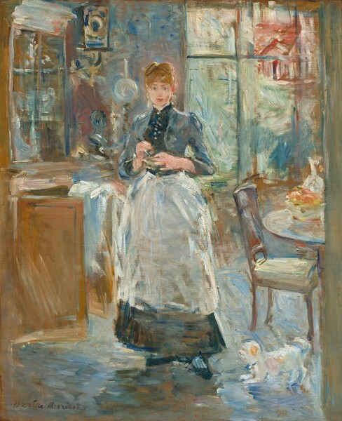 """A young woman with pale, peachy skin wearing a white apron over an ankle-length navy blue dress stands in a dining room in this vertical painting. The painting is created using loose brushstrokes throughout, giving the work a sense of movement and energy. The woman stands facing and looking out at us. Her auburn hair is pulled up into a bun and bangs sweep across her forehead. Her eyebrows are slightly raised, her deep pink lips are closed in the hint of a smile, and she holds her hands at her chest. Some details throughout the painting are indistinct because of the loose painting style but she might hold a mixing bowl. The high-necked bodice of the dress has buttons down the front and the apron falls to mid-shin. A tall curio cabinet fills the space to our left and brushes the top edge of the canvas. It seems to be filled with white or silver serving pieces and a white cloth is draped over one of the open cabinet doors below. A clock hangs on a wall over an oil lamp between the woman and curio cabinet. Light pours in through a tall window or French doors behind the girl to our right. Roughly painted forms suggest a house and landscape visible beyond. One chair is pulled up to a round table that is cut off by the right edge of the canvas. A decanter, perhaps glass, and bowl of peach- and rose-colored fruit sit on the table. A small white dog with tan spots scampers at the woman's feet near the chair. The artist signed the painting in brown in the lower left corner: """"Berthe Morisot."""""""