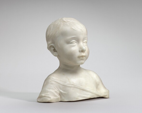 This white marble bust shows the head, shoulders, and upper chest of a young boy. The photograph was taken with the work angled slightly to our right. The boy has full cheeks, a slightly upturned nose, and short, wavy hair. He stares straight ahead, attentive and alert. His loose garment drapes from his right shoulder, on our left, down and across his chest to just below his left shoulder.