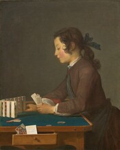 """Seen from about the lap up, a young person with brown hair and a peachy complexion, facing our left in profile, leans onto a table and sets folded cards up in a row in this vertical painting. Shown against a dark background, his long hair curls by his ears and is pulled back with a navy-blue ribbon at the nape of his neck. He has a delicately sloping nose, his pink lips are closed, the cheek facing us is flushed, and he looks down at the tabletop under lowered lids. He wears a chestnut brown, long-sleeved coat with a dark blue sash across his chest and tied around his waist. The white of his undershirt peeks out at the high neck and wrists, and the brick-red lining of the sleeve of his jacket rolls back at his right wrist. The wooden table is lined with teal fabric on its surface and three coins lie near his left hand, closer to us. In that hand he holds three nested, vertically folded playing cards. With his right hand he places the last in a line of ten cards, standing vertically but close together, in a curving row in front of him. Scarlet red diamonds and hearts and the edges of some black shapes are visible within the bent cards. A jack of hearts and a piece of paper or the back of another card sit in a drawer that opens towards us along the side of the table. The artist signed the work in dark brown paint in the lower right corner: """"J. Chardin."""""""