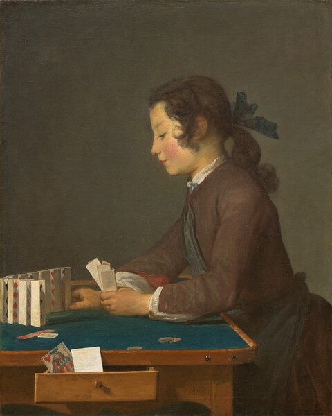 "Seen from about the lap up, a young person with brown hair and a peachy complexion, facing our left in profile, leans onto a table and sets folded cards up in a row in this vertical painting. Shown against a dark background, his long hair curls by his ears and is pulled back with a navy-blue ribbon at the nape of his neck. He has a delicately sloping nose, his pink lips are closed, the cheek facing us is flushed, and he looks down at the tabletop under lowered lids. He wears a chestnut brown, long-sleeved coat with a dark blue sash across his chest and tied around his waist. The white of his undershirt peeks out at the high neck and wrists, and the brick-red lining of the sleeve of his jacket rolls back at his right wrist. The wooden table is lined with teal fabric on its surface and three coins lie near his left hand, closer to us. In that hand he holds three nested, vertically folded playing cards. With his right hand he places the last in a line of ten cards, standing vertically but close together, in a curving row in front of him. Scarlet red diamonds and hearts and the edges of some black shapes are visible within the bent cards. A jack of hearts and a piece of paper or the back of another card sit in a drawer that opens towards us along the side of the table. The artist signed the work in dark brown paint in the lower right corner: ""J. Chardin."""