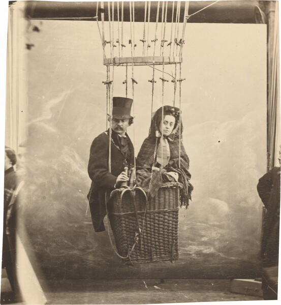A mustachioed white man and a woman crowd in the basket of a hot air balloon in this vertical, sepia-toned photograph. To our left, the man wears a tall top hat and a dark coat and cravat. His body angled slightly towards our right, he holds a pair of binoculars at his waist as he looks down and off to the side to our left. On our right, the woman wears a plaid patterned shawl that wraps around her body and seems to cover her head. A bow tied under her chin is a little wider than her face, and the wide ends reach far down her chest. She looks directly at us. The profile and torso of a studio assistant is cropped by the right edge. Building on that, upon closer inspection, we realize that the basket hangs a few feet above the floor in front of what must be a painted backdrop in a studio. The left edge is blurred and a sliver showing other people, or perhaps another exposure, is visible.
