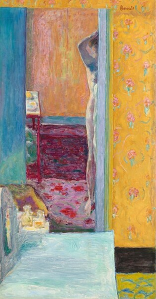 """What initially appears to be layered rectangles in marigold orange, butter yellow, rose pink, mauve, peach, aquamarine-blue, turquoise, and deep fuchsia comes into focus as one room seen in a reflection of a tall, rectangular mirror in front of us and to our left in this vertical painting. The left edge of a nude, pale-skinned woman holding at least one hand to her hair is reflected along the right edge of the mirror, which takes up the left two-thirds of the composition. Visible as a vertical strip to our right and a narrow strip along the top edge, the wall behind the mirror is papered with pale pink flowers with mint-green leaves against a field of golden yellow. A pale turquoise rectangle extends into the room from the lower left corner, and some perfume bottles sit beyond the far end. The floor of the room in the reflection is patterned with rounded, floral fuchsia shapes against a lilac purple background. A deep magenta field below an electric blue band suggests paneling beneath a chair rail. The wall above is streaked with peach, pink, and yellow. A frame-like table to our left at the back of the room perhaps holds embroidery. The woman's body is painted in tones of soft pink with cool blue shadows. She holds the arm and hand we can see up to her chestnut brown hair. Only the side of the head and ear, shoulder, arm, breast, hip, and her right leg are captured in the mirror. The scene is painted with loose, visible brushstrokes so some of the detail is difficult to make out, and it takes time to puzzle out what the scene captures. The artist signed the work with red paint in the upper right corner: """"Bonnard."""""""