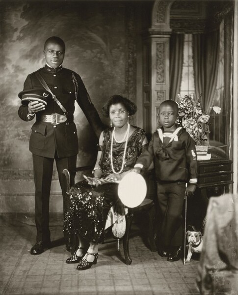 Three Black people formally pose with a man standing in a military uniform and a young child wearing a sailor suit flank a seated woman wearing a dark dress that shimmers with reflected light in this vertical photograph. The image is monochromatic like a black and white photograph but is printed in warm tones of golden and dark browns, almost black. The man and woman have slight smiles, and all three look at us. At the center, the slender woman sits on a wooden chair with her body angled slightly to our left, though she turns her head to us. Her skin tone is a little lighter than that of the man and boy, and her hair is styled in an ear-length bob. Her scoop-neck, sleeveless, ankle-length dress shimmers as if covered with beads or sequins. She wears round glasses, dangling earrings with pearls, and short and long strands of pearls. Light catches two rings on her left hand and a bangle bracelet encircles each arm. Her shiny, high-heeled shoes have a lattice-like pattern cut into the tops around the T-straps. She holds an object, perhaps with feathers, in her lap. The young, cleanshaven man to our left stands facing us with his weight equally balanced on both feet, positioned slightly apart. He rests his left hand, on our right, on the back of the woman's chair and holds his flat-topped, brimmed hat in the crook of his other elbow. His dark, crisply pressed uniform has a snug fitting jacket with a high collar, shiny buttons in a row down the front, and a braided cord looped over his left shoulder and under his arm. The jacket is cinched with a wide belt and a thin leather band runs diagonally across his chest. The boy, to our right, stands with one ankle crossed in front of the other and his right arm, on our left, resting on the arm of the woman's chair. In that hand, he holds what looks in the photograph like a bright white circle, likely the top of his hat. He rests his other hand near the top of a child-sized cane, close to his body. His hair is cut very short, li
