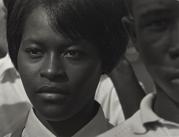 The face of a young Black woman fills most of this horizontal black and white photograph. The top of her head is cropped. She has straight black hair which sweeps down in bangs across her forehead and her hair is either cut short or pulled back. Her lips are closed and she looks steadily with dark eyes off into the distance to our left. Only the white or light-colored collar and very top of her right shoulder, on our left, are visible, though a dark narrow strap over her shoulder near her neck suggests a purse or backpack. She is positioned slightly to our left and to our right, the left half of a young Black man's face is cropped by the right edge of the photograph. He stands closer to us, in front of the woman's shoulder. His face is out of focus and he looks directly at the camera. More people fill the background between the woman and man but specific features are indistinguishable.