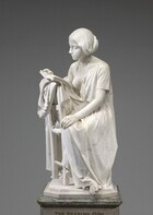 Carved from creamy white marble, a young girl sits turned to face the back of a wooden chair, where she props the open book she reads. In this photograph, her knees face us but her body and head are turned slightly to our left, towards the back of the chair, so we see her face almost in profile as she looks down at the book. Her long hair is loosely tied back at the nape of her neck. She has a straight nose and her lips are closed. A delicate tear falls from her left eye, closer to us. A short-sleeved garment like a nightgown falls open over her right shoulder so her breast is exposed. A medallion with a portrait of a man hangs from a long string around her neck. She holds the book open with her right hand, farther away from us, and her opposite hand rests in her lap. The book lies on more fabric bunching over the back of the straight wooden chair. Her bare feet, crossed at the ankle, peek out from under her long garment so that one foot extends beyond the marble base on which the chair rests.