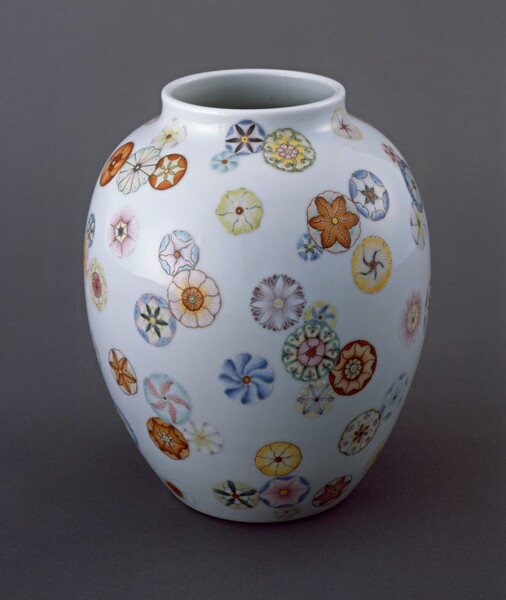 This white porcelain vase is almost egg-shaped, wider at the top and slightly tapered towards the bottom. The round opening at the top center has a low rim. The vase is decorated with circular, stylized flowers with almost geometric patterns made up of butter yellows, peach, ivory, pumpkin orange, and shades of blue. The blossoms seem randomly scattered so some cluster and overlap while others float alone.