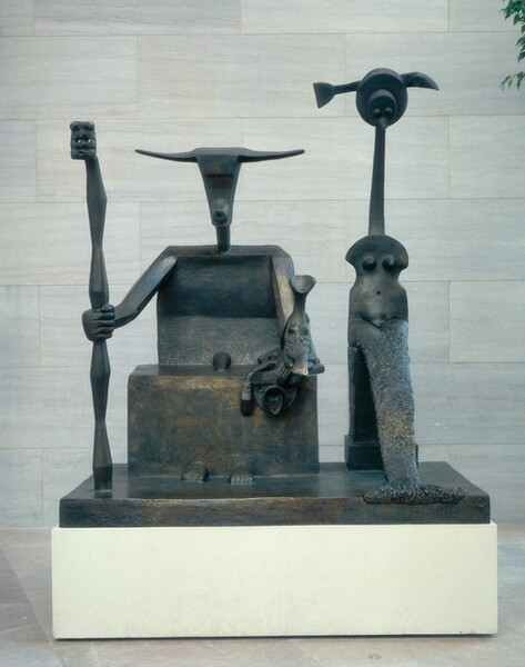 Two abstracted creatures, one resembling a goat holding a staff and the other a stylized mermaid, sit facing us on blocks on a rectangular base in this bronze sculpture. The head of the goat creature, to our left in this photograph, has wide horns to either side of a ridge suggesting a heavy brow. The triangular head tapers down to a ring that suggests the muzzle of the goat. The body is made up of broad geometric shapes. There is a stylized phallus where the body meets the block we read as a lap, and two rounded forms suggestive of human feet protrude from the base of that block. The creature reaches out with his right arm, to our left, to wrap a large, human fist around the staff. The staff swells and narrows in angular hourglass shapes and is topped by what could be a rectangular, abstracted face with two eye holes, a flattened nose, and a slit for a mouth. The goat's opposite hand rests near that knee, and in it he holds a creature about the height of the goat's torso. The creature has a scooped, cup-like form where the head would be, a long neck, and two mounds reminiscent of breasts above a textured fish's tail. Below, as if affixed to the front of the goat's lap, a disk-like face, like an emoji, has two rings for eyes and a tongue protruding from a round mouth. Other forms over the forehead and one next to the face read as flattened hands or claws. To our right, the second, taller creature has a head made up of a disk with two mounds for eyes and a beak stacked in front of a second, larger disk. A form like an abstracted fish or arrow moves through or behind her head. The creature has a long, slender neck and an armless torso, shaped roughly like the body of a violin. The torso has rounded shoulders, two mounds to suggest breasts, and a hole for a belly button. Her textured fish's tail curves down so the fin falls slightly over the front of the base on which they sit. The bronze surface of the sculpture varies from dark brown to faint gold where the light cat