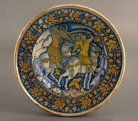 Large dish with running plant border; in the center, horsemen fighting