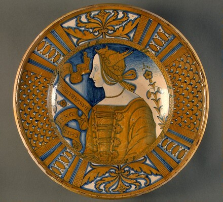 Large dish with segmental border of plant sprays and scale pattern; in the center, a profile bust of a woman in a winged headdress
