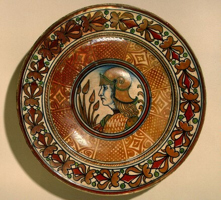Plate with running plant border and geometric panels on well; in the center, profile bust of a man in armor