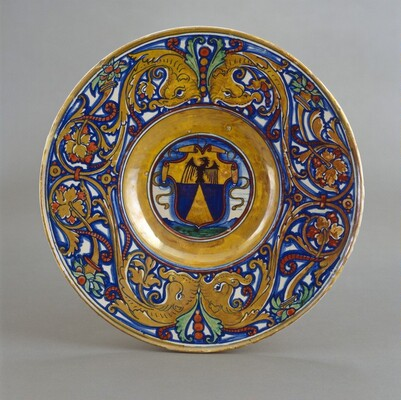 Plate with border of foliate scrollwork with dolphin heads and cornucopias; in the center, shield of arms of Vigerio of Savona