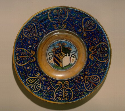 Plate with border of palmettes and scrollwork; in the center, a shield of arms and the initials A.F.
