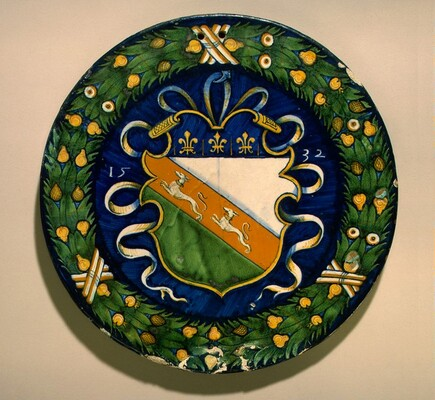 Circular plaque with fruited wreath enclosing a shield of arms
