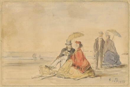 A Couple Seated and a Couple Walking on the Beach