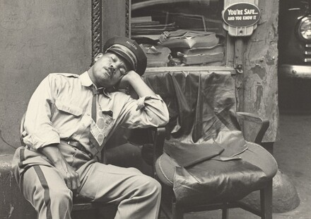 At the same time Mel, his morning duties done, has changed his uniform and rests in one of the garage chairs.