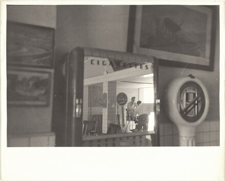 Shining shoes, reflection in cigarette machine mirror--New Mexico
